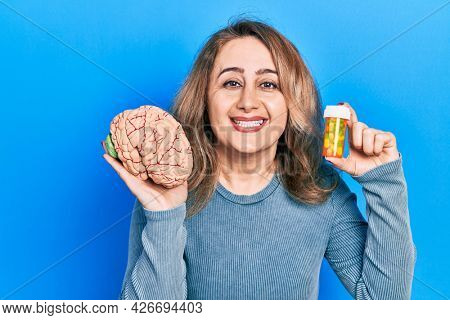 Middle age caucasian woman holding brain and pills as mental health concept smiling and laughing hard out loud because funny crazy joke.