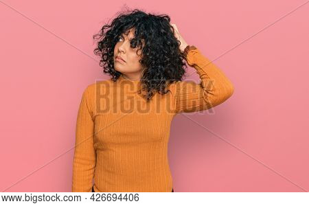 Young hispanic woman wearing casual clothes confuse and wondering about question. uncertain with doubt, thinking with hand on head. pensive concept.