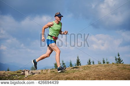 Full Length Of Muscular Young Man Running Up The Hill With Blue Cloudy Sky On Background. Handsome M