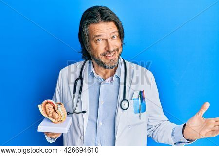 Middle age handsome gynecologist man holding anatomical model of female uterus with fetus celebrating achievement with happy smile and winner expression with raised hand