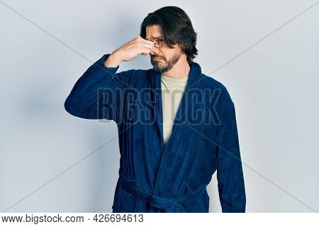Middle age caucasian man wearing bathrobe and glasses smelling something stinky and disgusting, intolerable smell, holding breath with fingers on nose. bad smell