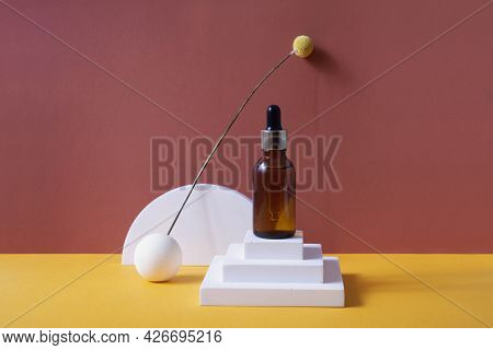 Amber Glass Dropper Bottle With Metallic Lid On The White Podium. Orange And Terracotta Background.