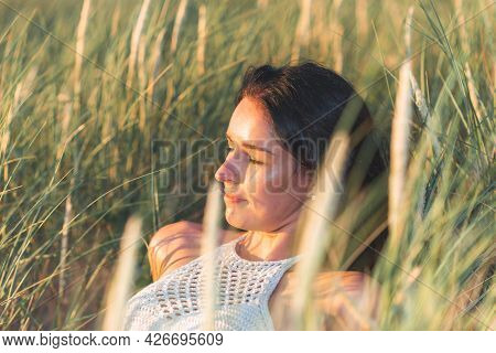 Portrait Of A Beautiful Young Woman On Meadow Watching The Sunset Enjoying Nature Summer Evening Out