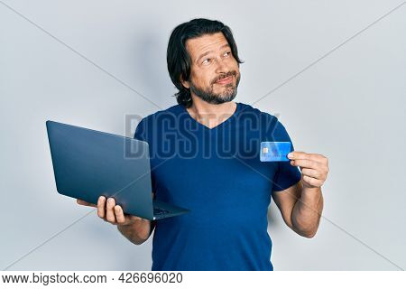 Middle age caucasian man wearing business style holding laptop and credit card smiling looking to the side and staring away thinking.