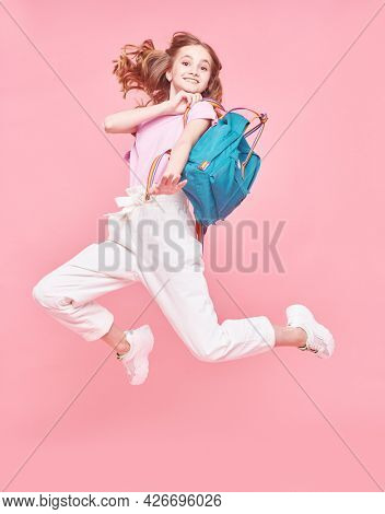 Joyful student girl teenager in casual summer clothes jumping on a pink background. Happiness and active lifestyle. Youth style. Holidays.