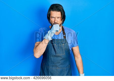Middle age caucasian man wearing cleaner apron and gloves feeling unwell and coughing as symptom for cold or bronchitis. health care concept.