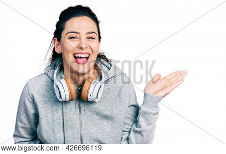 Young hispanic woman wearing gym clothes, using headphones and smart watch smiling and laughing hard out loud because funny crazy joke.