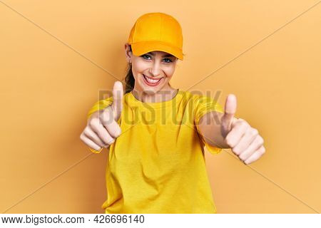 Young hispanic woman wearing delivery uniform and cap approving doing positive gesture with hand, thumbs up smiling and happy for success. winner gesture.