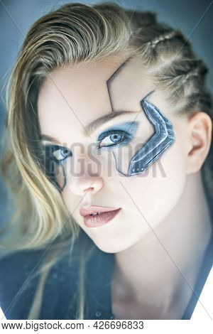 Close-up portrait of an attractive sci-fi cyborg girl. Cyberpunk concept. Make-up and hairstyle.
