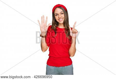 Young brunette woman wearing casual clothes showing and pointing up with fingers number seven while smiling confident and happy.