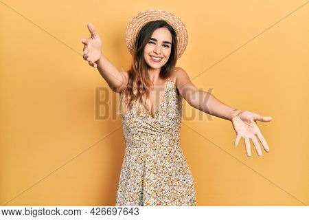 Young hispanic girl wearing summer hat looking at the camera smiling with open arms for hug. cheerful expression embracing happiness.