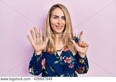 Young caucasian woman wearing casual clothes showing and pointing up with fingers number seven while smiling confident and happy.