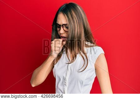 Young brunette woman wearing casual clothes and glasses feeling unwell and coughing as symptom for cold or bronchitis. health care concept.