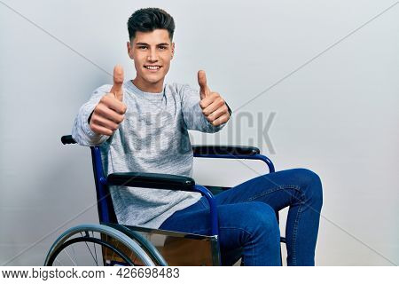 Young hispanic man sitting on wheelchair approving doing positive gesture with hand, thumbs up smiling and happy for success. winner gesture.