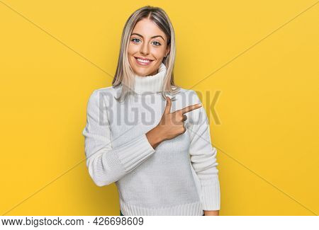 Beautiful blonde woman wearing casual turtleneck sweater cheerful with a smile of face pointing with hand and finger up to the side with happy and natural expression on face
