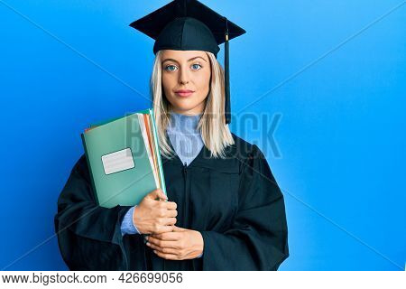 Beautiful blonde woman wearing graduation cap and ceremony robe holding books thinking attitude and sober expression looking self confident