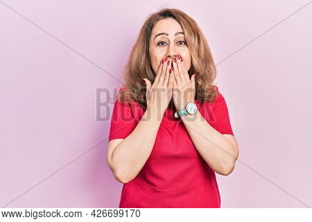 Middle age caucasian woman wearing casual clothes laughing and embarrassed giggle covering mouth with hands, gossip and scandal concept