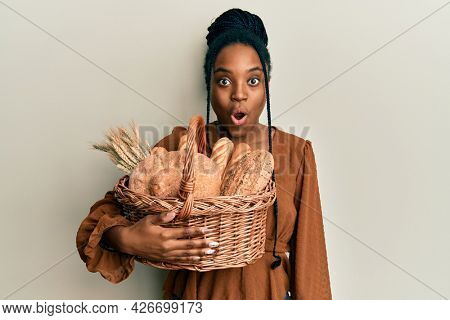 African american woman with braided hair holding wicker basket with bread scared and amazed with open mouth for surprise, disbelief face