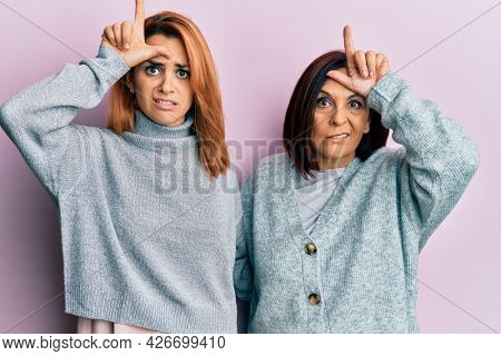 Latin mother and daughter wearing casual clothes making fun of people with fingers on forehead doing loser gesture mocking and insulting.