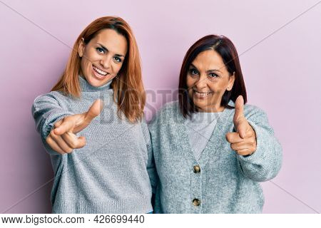 Latin mother and daughter wearing casual clothes pointing fingers to camera with happy and funny face. good energy and vibes.