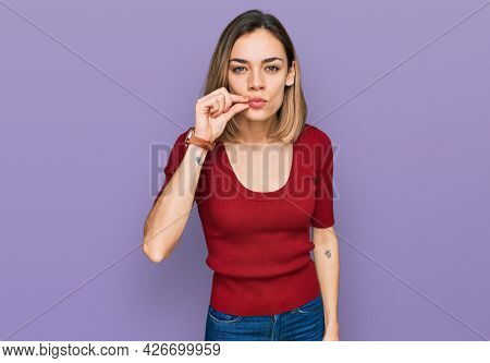 Young blonde girl wearing casual clothes mouth and lips shut as zip with fingers. secret and silent, taboo talking