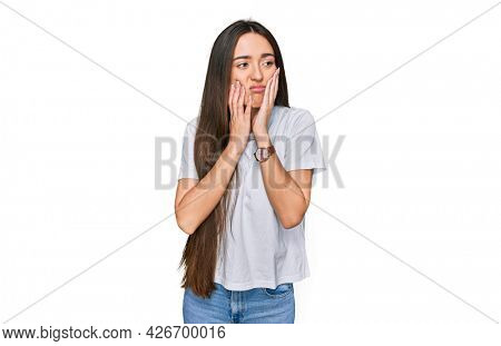 Young hispanic girl wearing casual white t shirt tired hands covering face, depression and sadness, upset and irritated for problem