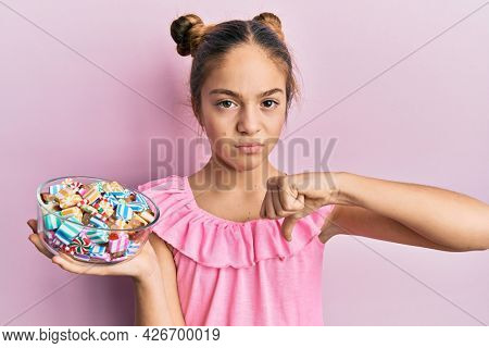 Beautiful brunette little girl holding jar full of sugar candies with angry face, negative sign showing dislike with thumbs down, rejection concept