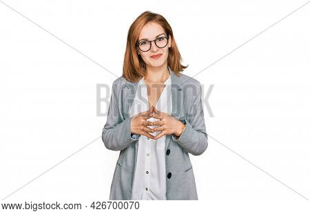 Young caucasian woman wearing business style and glasses hands together and fingers crossed smiling relaxed and cheerful. success and optimistic