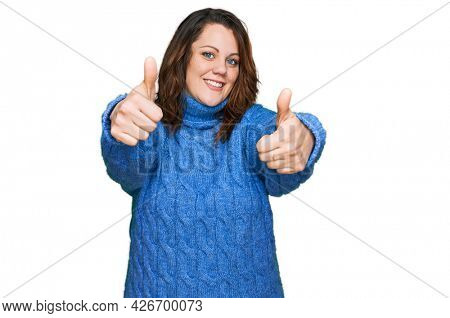 Young plus size woman wearing casual clothes approving doing positive gesture with hand, thumbs up smiling and happy for success. winner gesture.
