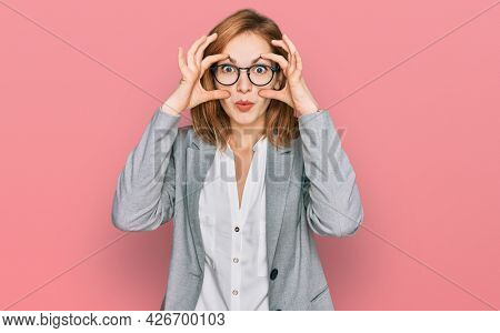 Young caucasian woman wearing business style and glasses trying to open eyes with fingers, sleepy and tired for morning fatigue