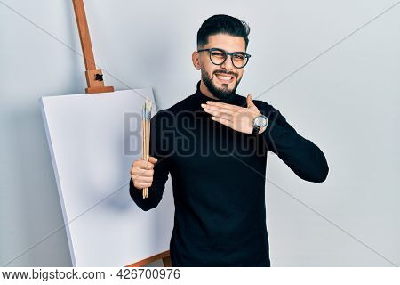 Handsome man with beard holding brushes close to easel stand cutting throat with hand as knife, threaten aggression with furious violence