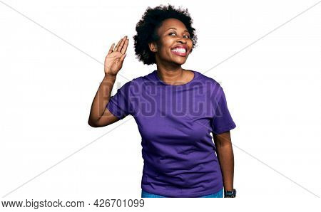 African american woman with afro hair wearing casual purple t shirt waiving saying hello happy and smiling, friendly welcome gesture