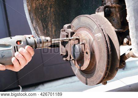 Car Repair. A Car Mechanic Drills A Hole In The Wheel Hub For A Repair Thread.
