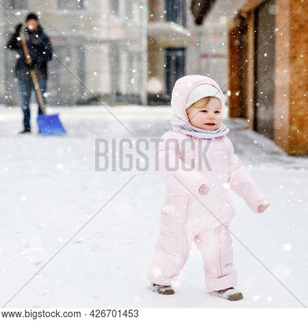 Adorable Little Baby Girl Making First Steps Outdoors In Winter Through Snow. Cute Toddler Child Lea