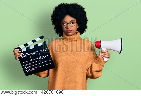 Young african american woman holding video film clapboard and megaphone relaxed with serious expression on face. simple and natural looking at the camera.