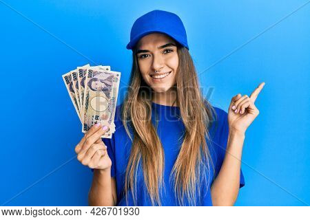 Young hispanic woman wearing delivery uniform and cap holding japanese yuan smiling happy pointing with hand and finger to the side