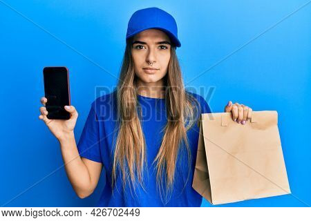Young hispanic woman holding delivery paper bag and showing smartphone screen relaxed with serious expression on face. simple and natural looking at the camera.