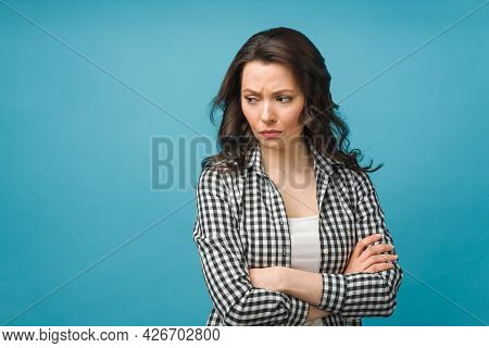 Portrait Of An Angry Young Woman Standing Over Isolated Blue Background.