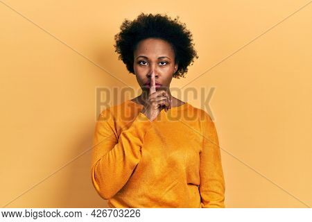 Young african american woman wearing casual clothes asking to be quiet with finger on lips. silence and secret concept.