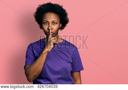 African american woman with afro hair wearing casual purple t shirt asking to be quiet with finger on lips. silence and secret concept.