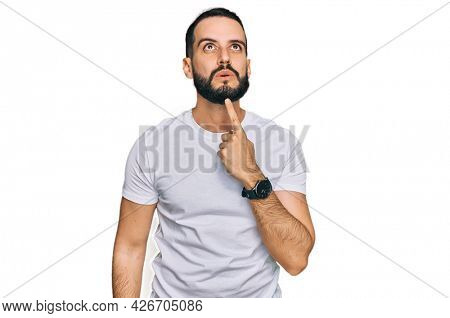 Young man with beard wearing casual white t shirt thinking concentrated about doubt with finger on chin and looking up wondering