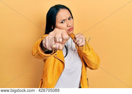 Beautiful hispanic woman with nose piercing wearing yellow leather jacket punching fist to fight, aggressive and angry attack, threat and violence