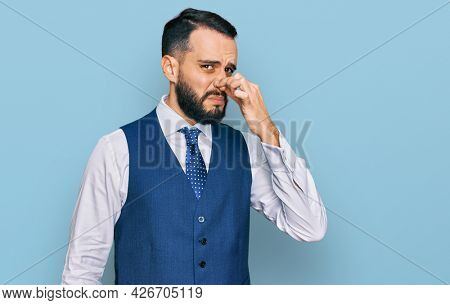 Young man with beard wearing business vest smelling something stinky and disgusting, intolerable smell, holding breath with fingers on nose. bad smell