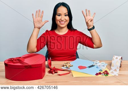 Beautiful hispanic woman with nose piercing doing handcraft creative decoration showing and pointing up with fingers number nine while smiling confident and happy.