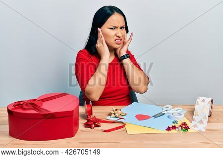 Beautiful hispanic woman with nose piercing doing handcraft creative decoration covering ears with fingers with annoyed expression for the noise of loud music. deaf concept.