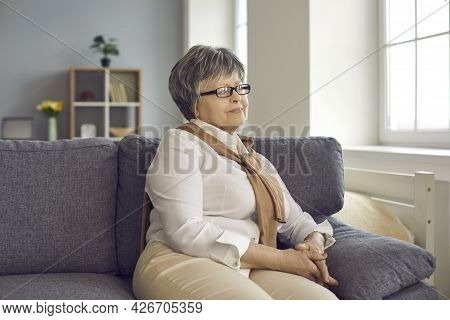 Portrait Of Happy Retired Mature Woman Sitting On Couch At Home And Looking Away
