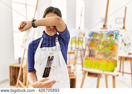 Young brunette woman at art studio covering eyes with arm, looking serious and sad. sightless, hiding and rejection concept