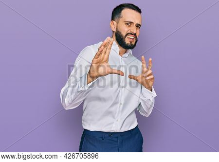 Young man with beard wearing business shirt disgusted expression, displeased and fearful doing disgust face because aversion reaction. with hands raised
