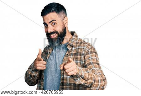 Hispanic man with beard wearing casual shirt pointing fingers to camera with happy and funny face. good energy and vibes.