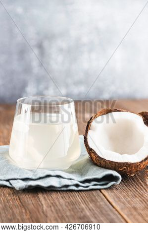 A Glass Of Fresh, Organic Coconut Water, Milk On A Wooden Table And Half A Juicy Coconut Next To It.